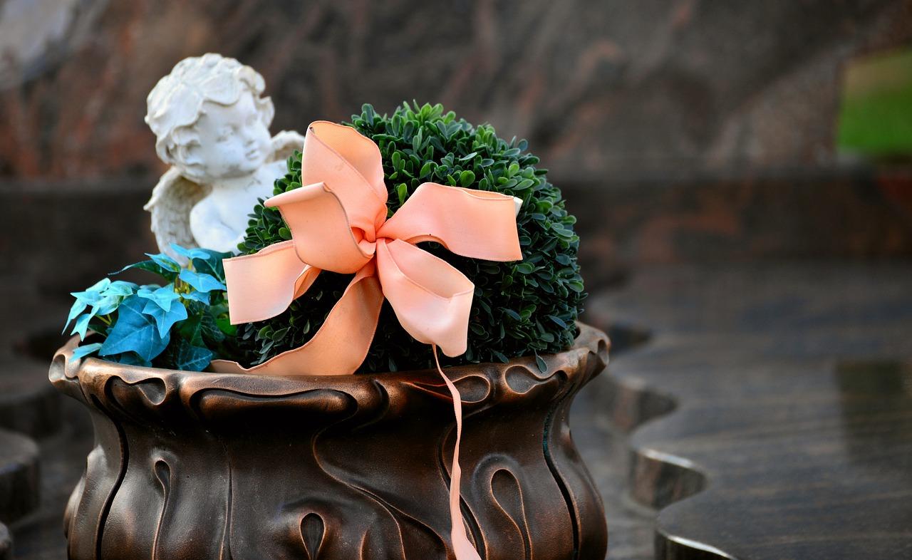 Dekoračná váza s anjelom a slabo oranžovou mašľou